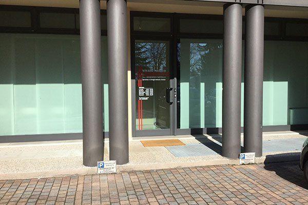 due colonne portanti di uno stabile e dietro un'entrata con una porta in vetro