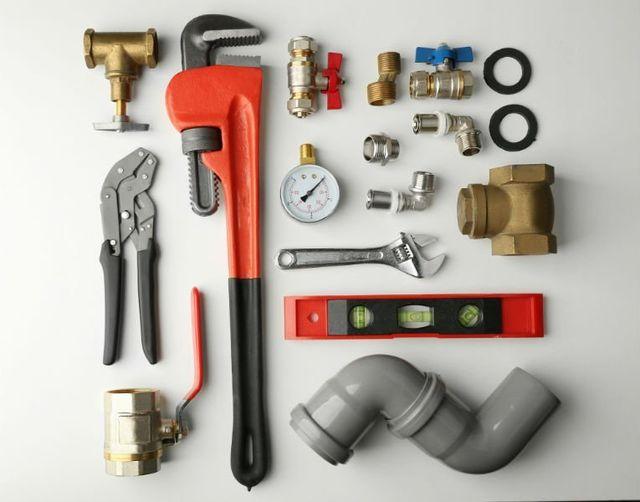 attrezzature per elettricista come tubo, martello e chiave inglese.