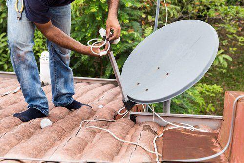 un uomo sul tetto ripara un'antenna