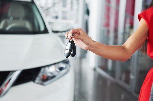 Una donna mostra le chiavi di un auto appena noleggiata