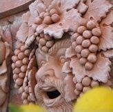maschera in terracotta con grappoli d'uva