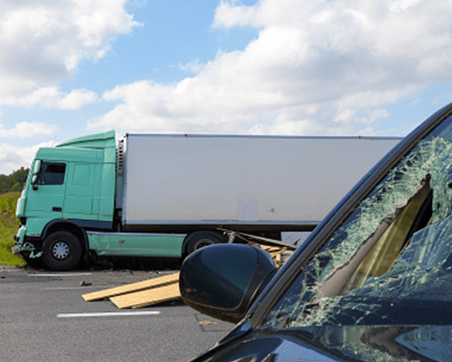 una macchina con il parabrezza rotto e un camion uscita fuoristrada