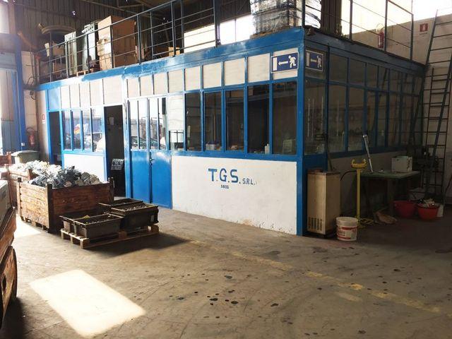 una struttura cabinata all'interno della fabbrica con scritto TGS