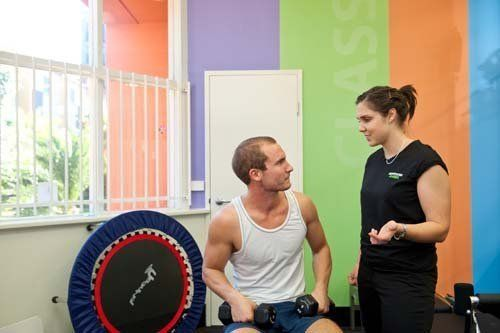 Personal trainer helping the customer