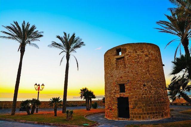 una torretta antica in mattoni, delle palme e vista del tramonto