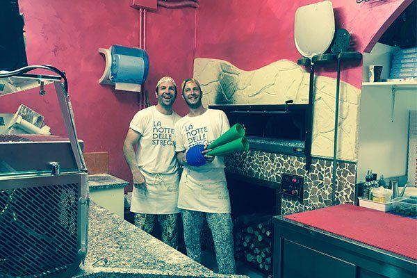due pizzaioli in posa per una foto vicino a un forno a legna