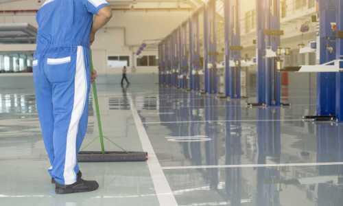 Operatore impresa pulizie che lava un pavimento