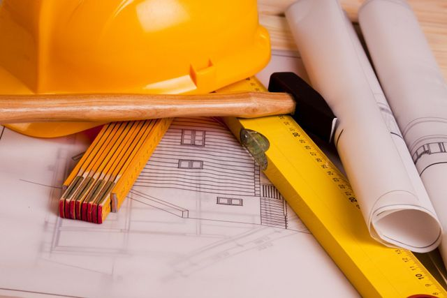 Home plans are laid out on a table, with measuring devices and a hard hat