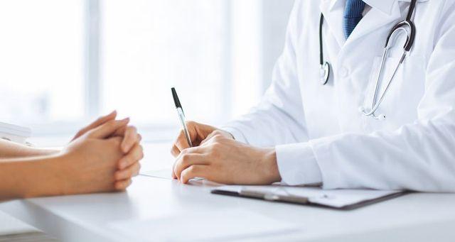 un dottore seduto alla scrivania con camice bianco,stetoscopio e una penna in mano e di fronte le mani di una donna