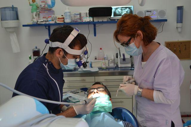 un dentista con camice color verde smeraldo e mascherina sta mostrando un impianto dentale a una ragazza con una mantella dello stesso colore del camice del dentista mentre e' seduta sul lettino