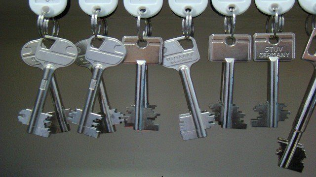 A row of keys hanging from white fobs
