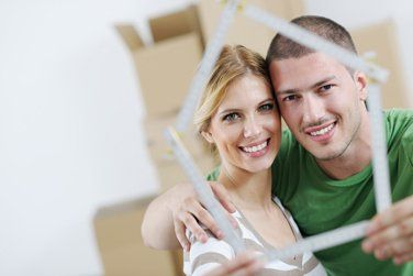 couple posing with the frame of a house