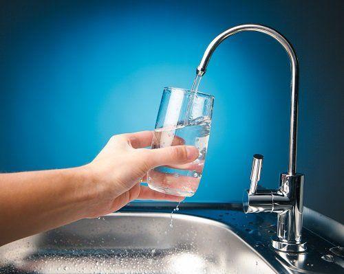 Mano, sostenendo un bicchiere che si riempie di acqua del rubinetto