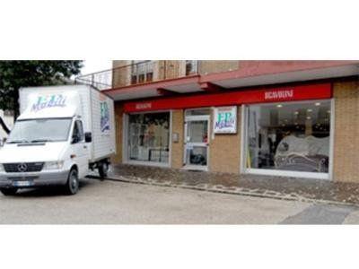 vista esterna del negozio con un camion bianco parcheggiato