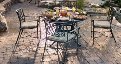 Iron table laid for lunch, surrounded by four chairs, on a patio