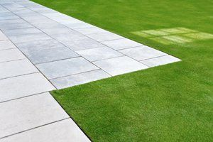 Pale grey paving against a green lawn