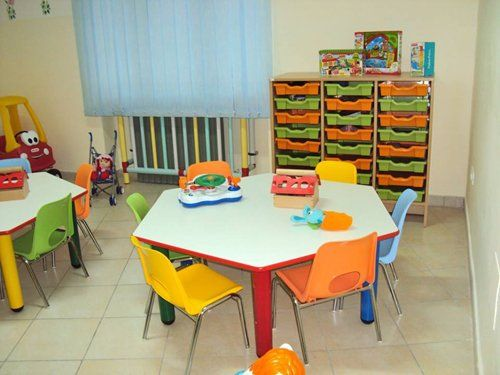 tavolo basso esagonale con sedie colorate in un asilo