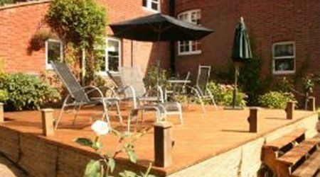 Sun loungers and parasol on raised decking