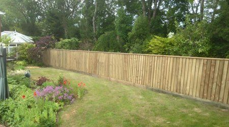 Flower beds in the centre of a garden with timber fencing