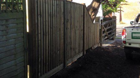 A tall dark timber fence and gate