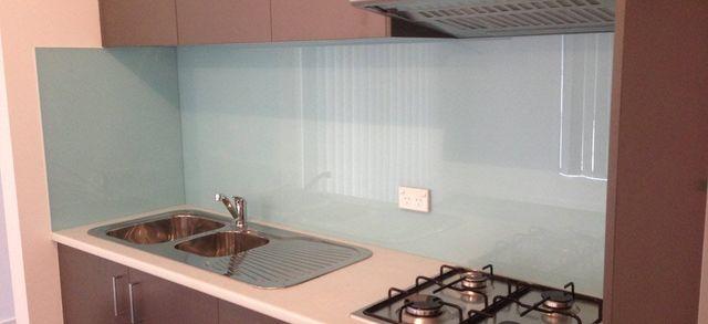pink kitchen with glass splashback