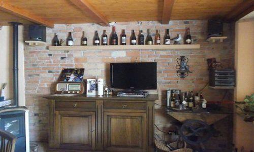 un mobile di legno con una TV e una mensola con delle bottiglie