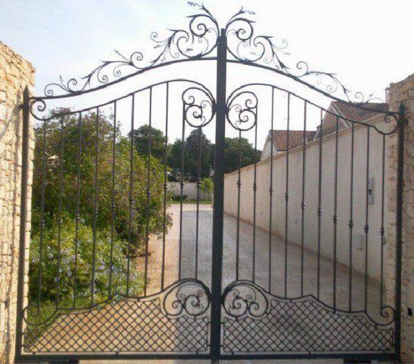 un cancello nero in ferro battuto chiude un vialetto