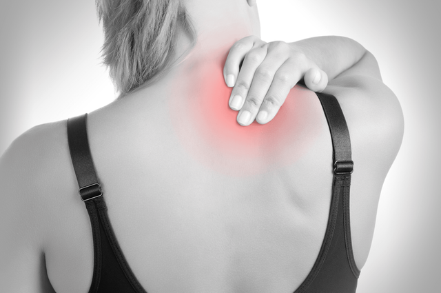 Black and white shot of lady with her hand on the back of her neck where painful spot is highlighted in red