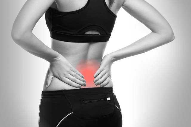 Lady with her hands on a painful spot on her lower back, highlighted in red