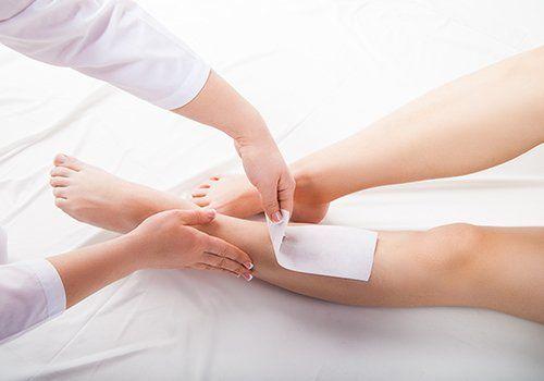 due mani che tolgono una striscia epilatoria da una gamba di una donna