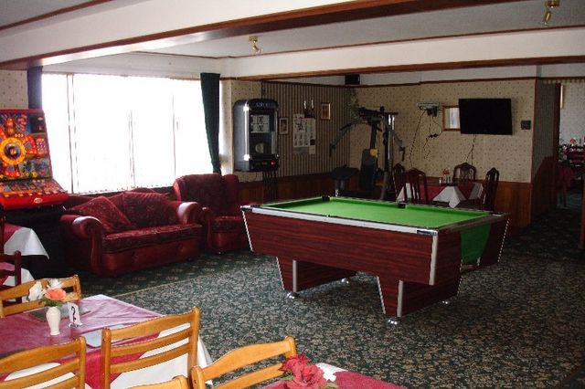 large room with red sofa and a pool table in the middle