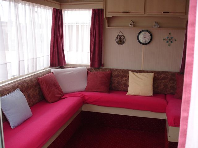 a room with a red couch and multiple pillows and windows