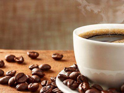 tazza di caffe con dei chicchi vicino