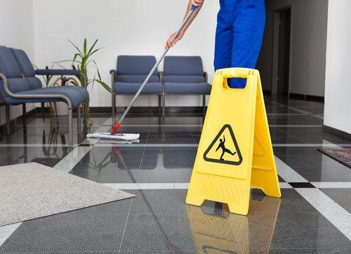 un cartello di pericolo di scivolare e un inserviente che pulisce per terra con un mocio
