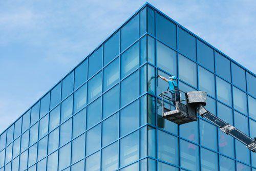 un uomo su una piattaforma all'esterno di un edificio mentre pulisce i vetri
