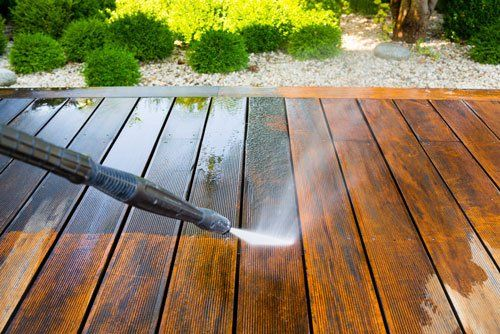 un'idropulitrice che schizza dell'acqua su una pavimentazione in legno