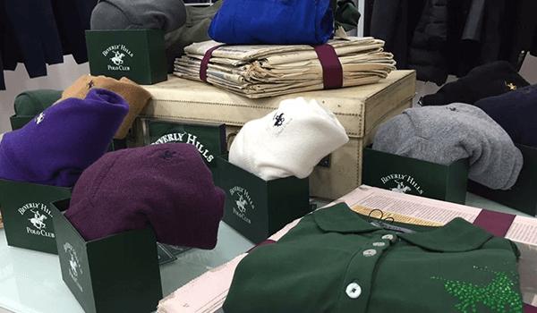 magliette, pantaloni e maglioni di diversi colori della marca Beverly Hills Polo Club all'interno di scatole verdi a Bari