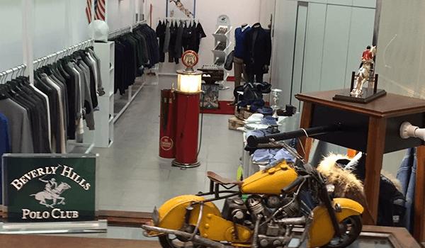 interno del negozio con abbigliamento appeso sul lato sinistro, bandiera americana, modellino di una moto gialla e logo Beverly Hills Polo Club a Bari