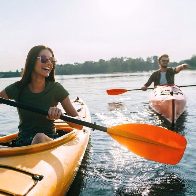 A young couple smiling while kayaking