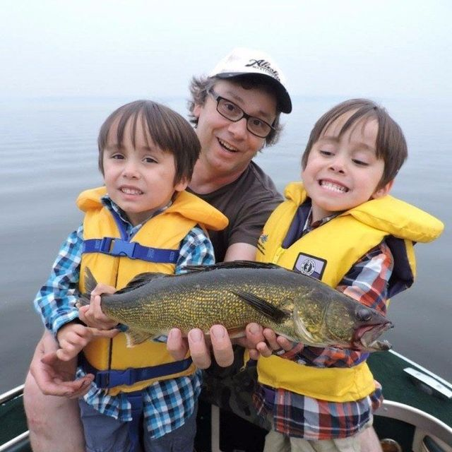 Photo of a man with two boys holding a freshly caught fish