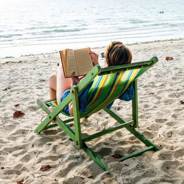 A woman reading a book while sitting on a chair