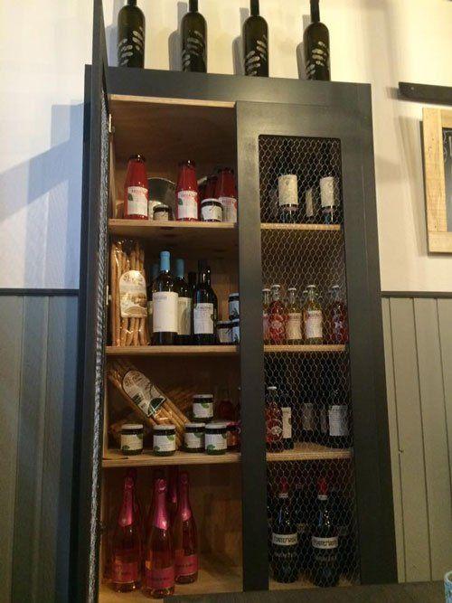 una credenza con dentro delle bottiglie di vino,vasetti, grissini e delle bottiglie di passata di pomodoro
