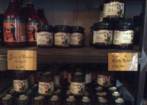 delle bottiglie di salsa di pomodoro e altri vasetti in un armadio