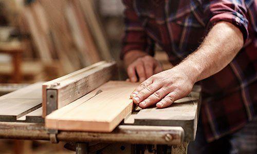 un uomo con una camicia scozzese blu e bordeaux al ,lavoro su un asse di legno