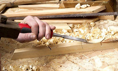 una mano con un cacciavite al lavoro su del legno chiaro e accanto vista del truciolato
