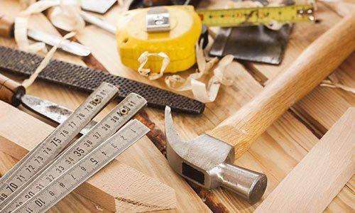 un metro giallo,un martello,una spatola e altri attrezzi appoggiati su un tavolo di legno