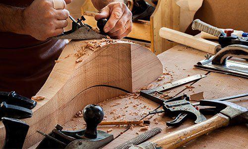 due mani al lavoro su un pezzo di legno e di fronte degli attrezzi del mestiere sul banco da lavoro