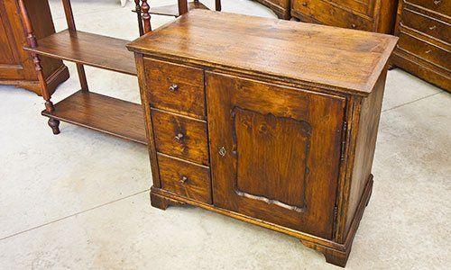un mobiletto in legno antico all'interno di un negozio con accanto altri mobili in legno