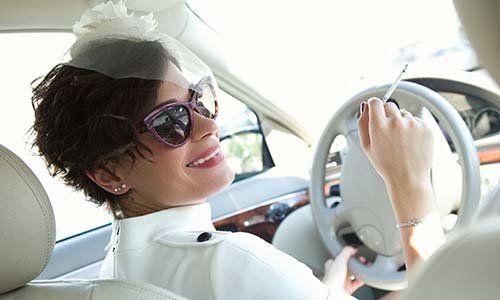 una donna al volante con una sigaretta