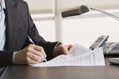 Uomo siglando alcuni documenti
